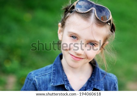 Outdoor portrait of a cute child girl with sunglasses looking at camera - stock photo