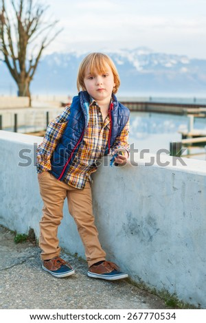 Outdoor portrait of a cute fashion little boy of 4 years old, wearing blue waistcoat, plaid shirt, beige trousers and sneakers - stock photo