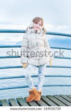 Outdoor portrait of a cute girl on a bridge on a nice winter day, wearing white jacket, printed jeans and brown boots - stock photo