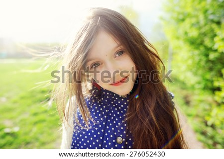 Outdoor portrait of a cute kid girl with long brunette hair on sunset, playing in the park - stock photo
