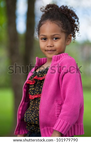 Outdoor portrait  of a cute little African Asian girl - stock photo