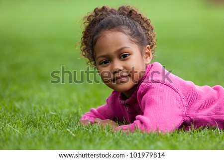 Outdoor portrait  of a cute little African Asian girl lying down on the grass - stock photo