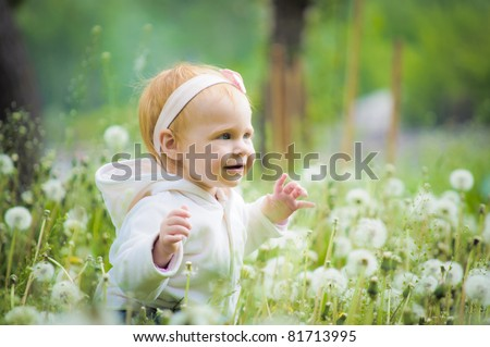 Outdoor portrait of a cute little baby in the grass - stock photo