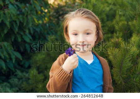 Outdoor portrait of a cute little boy of 4 years old, holding first spring flowers violets, toned image - stock photo
