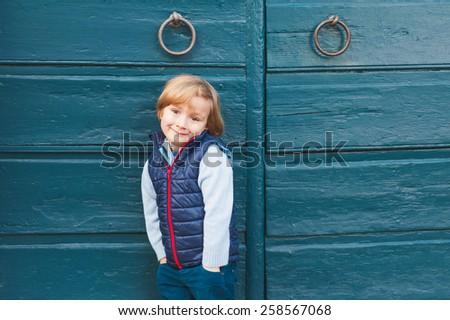 Outdoor portrait of a cute little boy wearing blue waistcoat, standing next to blue wooden door - stock photo