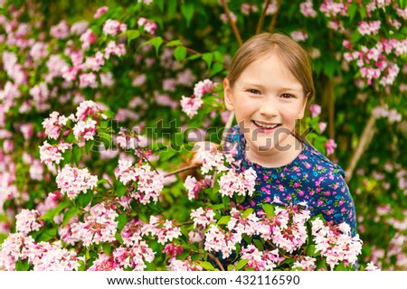 Outdoor portrait of a cute little girl of 8-9 years old, playing with spring flowers - stock photo