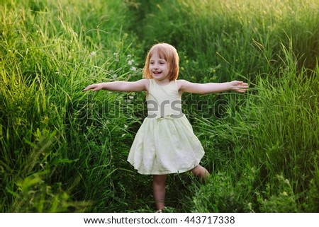 Outdoor portrait of a cute little girl playing in the grass, childhood, happiness, nature, relaxation - stock photo