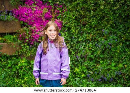 Outdoor portrait of a cute little girl under the rain, pulling her tongue, wearing purple rain coat - stock photo