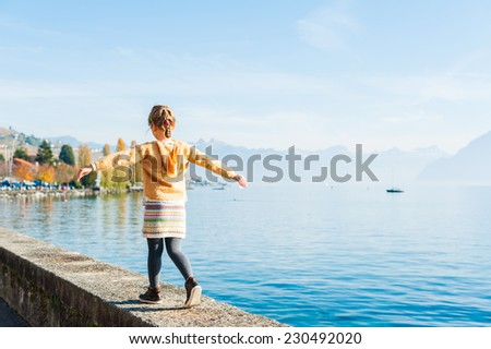 Outdoor portrait of a cute little girl walking next to beautiful lake - stock photo