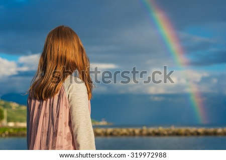 Outdoor portrait of a cute little girl watching the rainbow, back view - stock photo