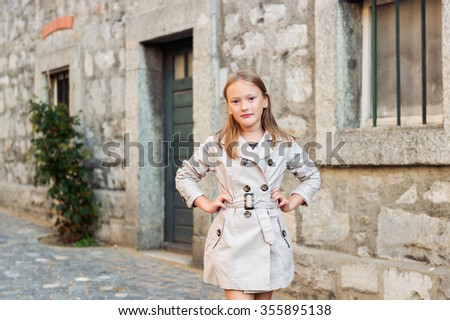 Outdoor portrait of a cute little girl, wearing beige coat - stock photo