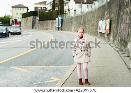 Outdoor portrait of a cute little girl, wearing beige coat and red shoes - stock photo
