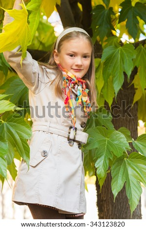 Outdoor portrait of a cute little girl wearing beige trench coat - stock photo