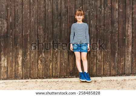 Outdoor portrait of a cute little girl, wearing frock, denim skirt and beautiful blue sneakers, standing against brown wooden wall - stock photo