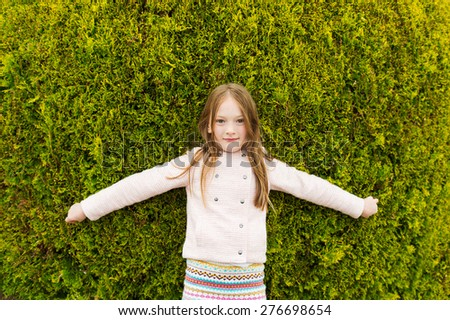 Outdoor portrait of a cute little girl wearing jacket, playing with a big bush - stock photo