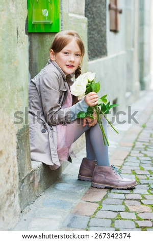 Outdoor portrait of a cute little girl with white roses, wearing beige coat and boots, sitting on steps in the old town - stock photo