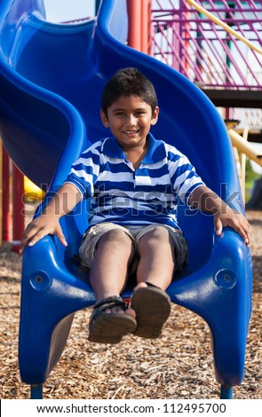 Outdoor portrait of a cute little indian boy at playground - stock photo