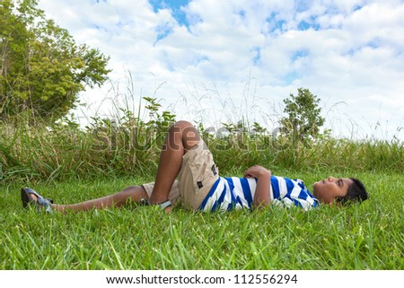 Outdoor portrait of a cute little indian boy looking to the sky - stock photo