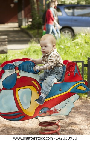 Outdoor portrait of a cute serious baby boy playing at playground - stock photo