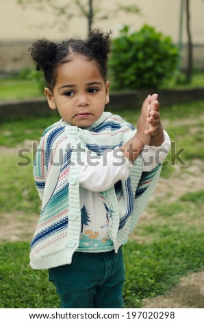 Outdoor portrait of a cute young black baby girl - stock photo