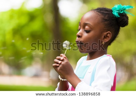 Outdoor portrait of a cute young black girl blowing a dandelion flower - African people - stock photo