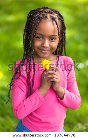 Outdoor portrait of a cute young black girl holding a dandelion flower - African people - stock photo