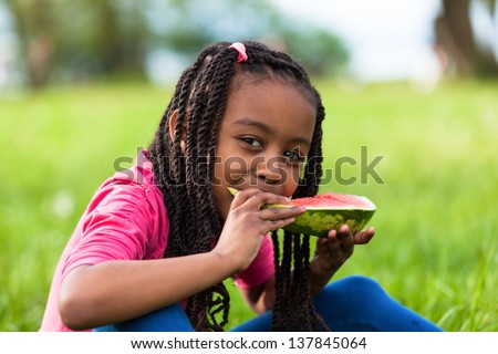 Outdoor portrait of a cute young black little  girl eating watermelon - African people - stock photo
