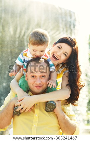 outdoor portrait of a family. young parents with a baby for a walk in the summer park. Mom, dad and child