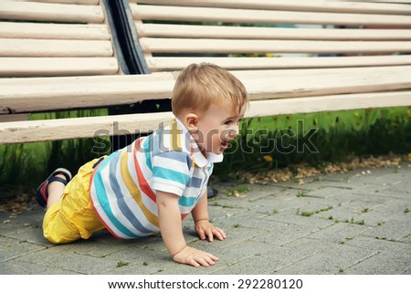 outdoor portrait of a funny playful boy. happy child on walk in the summer park - stock photo
