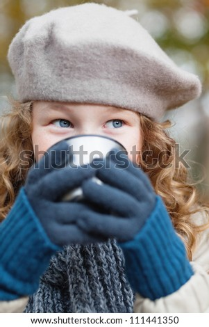 Outdoor portrait of a girl in winter cloths drinking from flask cup - stock photo