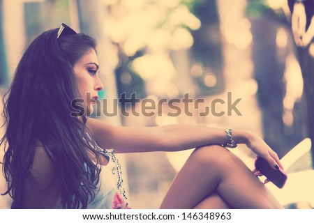 outdoor portrait of a girl sitting holding cell phone in hand side view retro colors
