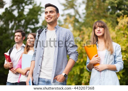 Outdoor portrait of a group of students. Shallow depth of field, focus on the guy in the center