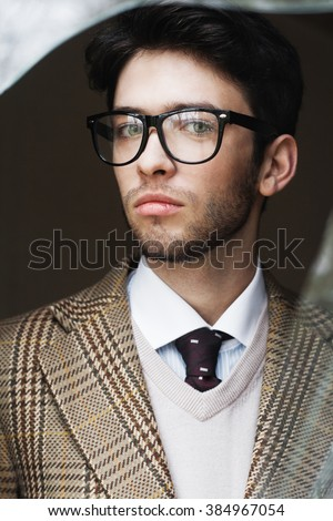Outdoor portrait of a handsome stylish man wearing glasses - stock photo