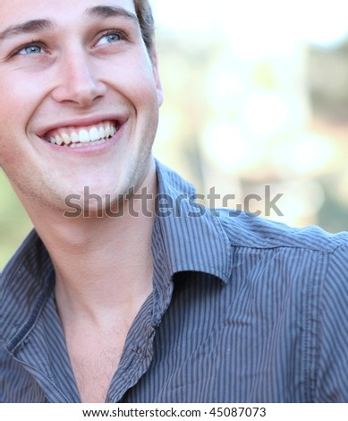 Outdoor portrait of a handsome young casual smiling man - stock photo