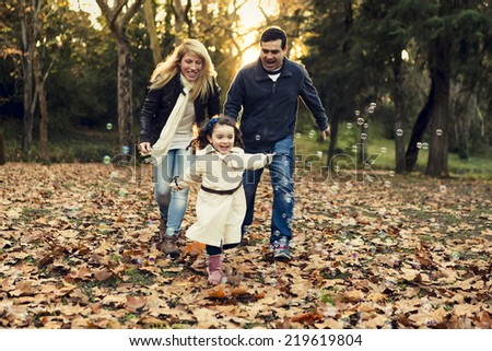 Outdoor portrait of a happy family enjoying the fall season - stock photo