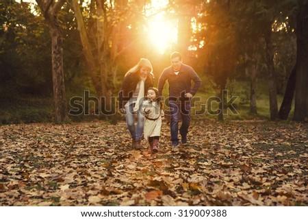 Outdoor portrait of a happy family enjoying the fall season - stock photo
