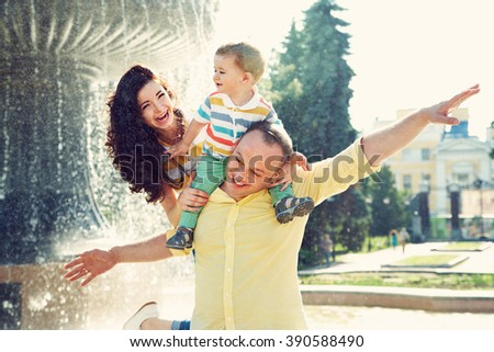 outdoor portrait of a happy family. young parents with a baby for a walk in the summer park. Mom, dad and child - stock photo