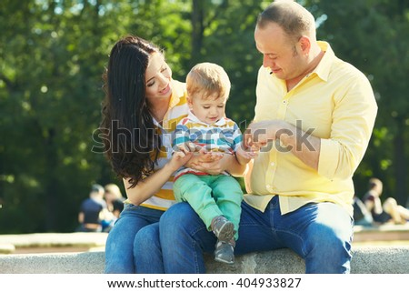 outdoor portrait of a happy family. young parents with a baby for a walk in the summer park. Mom, dad and child