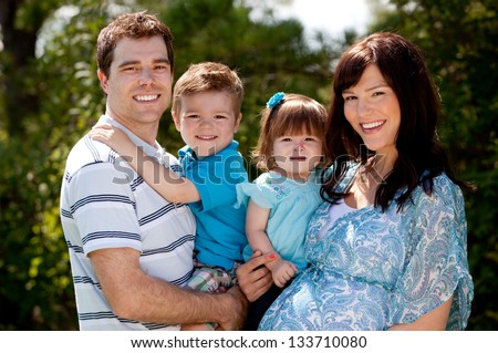 Outdoor portrait of a happy young family with pregnant mother - stock photo