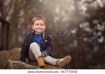 outdoor portrait of a little boy sitting on rocks - stock photo