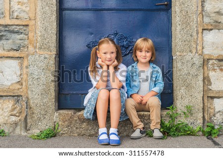 Outdoor portrait of a little girl and her brother - stock photo