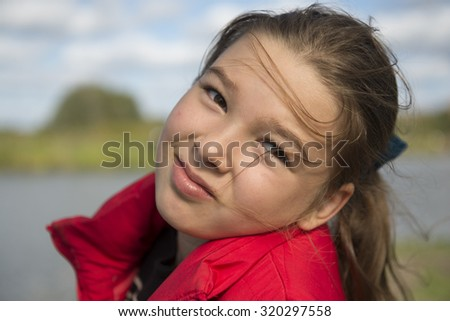 Outdoor portrait of a little girl in a red jacket - stock photo