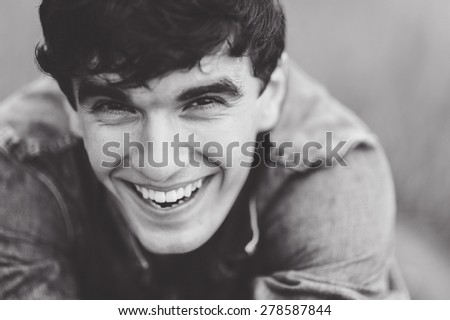 outdoor portrait of a manly  very beautiful sexy young man, dark hair, with a stunning smile, smiling and posing in the green grass in a white shirt and a denim jacket  as the Italian - stock photo