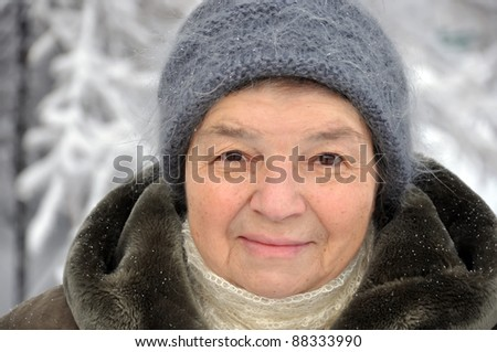 Outdoor portrait of a old woman in winter clothes