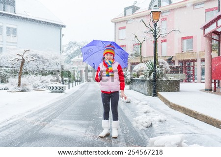 Outdoor portrait of a pretty little girl in a city under the snowfall - stock photo