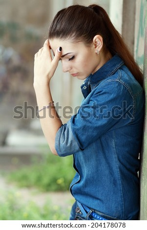 Outdoor portrait of a sad teenage girl looking thoughtful about troubles
