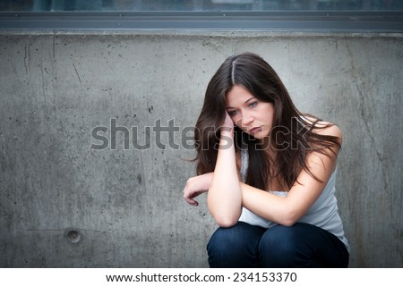 Outdoor portrait of a sad teenage girl looking thoughtful about troubles in front of a gray wall