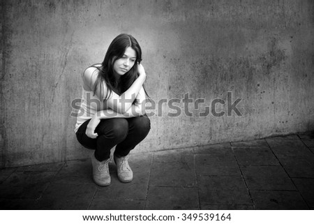 Outdoor portrait of a sad teenage girl looking thoughtful about troubles in front of a gray wall, black and white photo with copy space on the right side of the image - stock photo