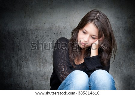 Outdoor portrait of a sad teenage girl looking thoughtful about troubles in front of a gray wall, copy space on the left side of the image - stock photo