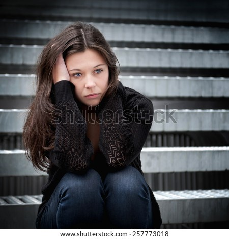 Outdoor portrait of a sad teenage girl looking thoughtful about troubles sitting on stair - stock photo